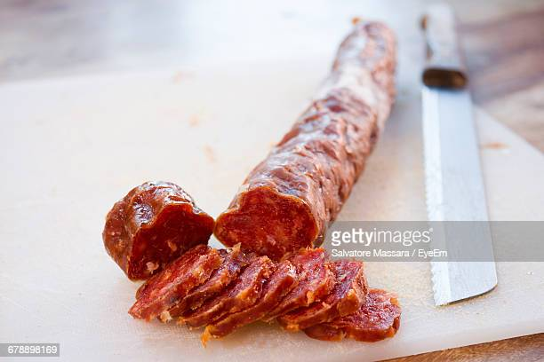 close-up of sliced salami with knife on cutting board - pepperoni stock photos and pictures