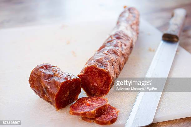 Close-up Of Sliced Salami With Knife On Cutting Board