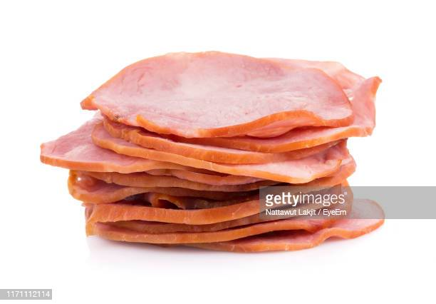 close-up of sliced stacked hams against white background - ham stock pictures, royalty-free photos & images