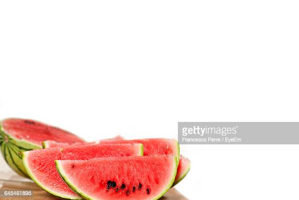 Close-Up Of Sliced Watermelons On Table Against White Background