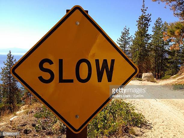 Close-Up Of Slow Sign By Dirt Road Against Blue Sky