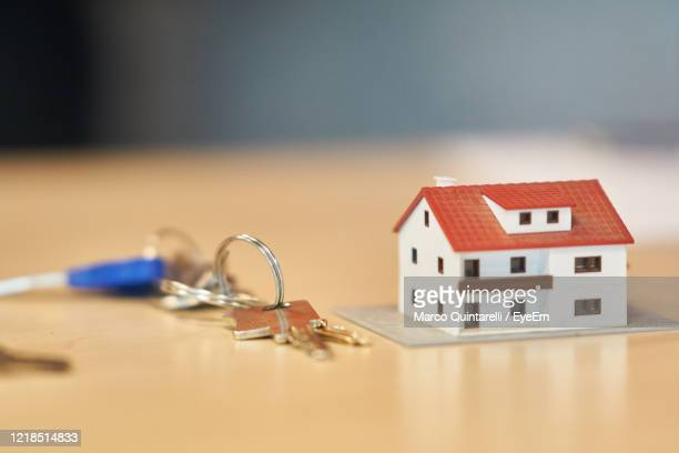 close-up of small house on table against building. real estate business - commercial real estate sign stock pictures, royalty-free photos & images