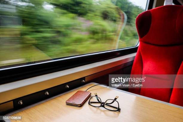Close-Up Of Smart Phone And Eyeglasses On Table In Train