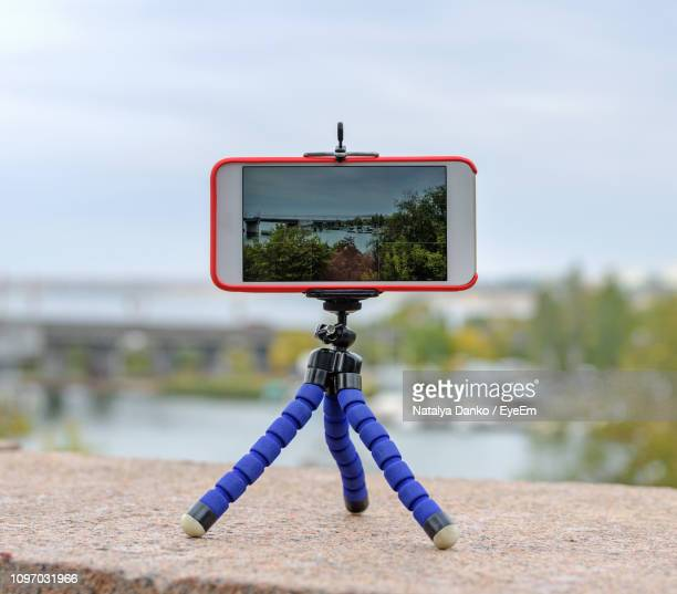 close-up of smart phone in tripod on retaining wall against sky - tripod stock pictures, royalty-free photos & images