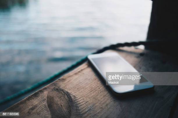 Close-up of smart phone on jetty over lake