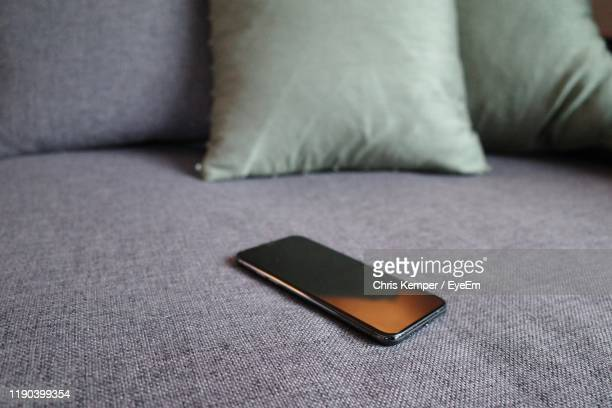 close-up of smart phone on sofa - sofa stock pictures, royalty-free photos & images
