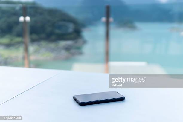 close-up of smart phone on the table at balcony - shallow stock pictures, royalty-free photos & images