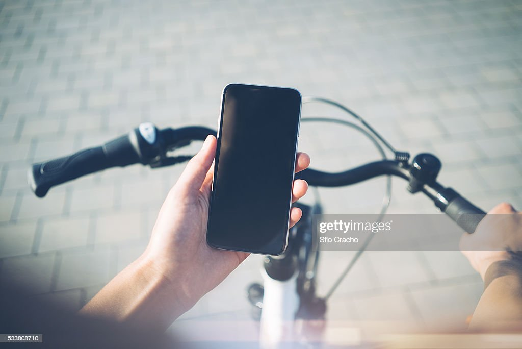 Close-up of smartphone in hands of young woman on bicycle : Foto stock