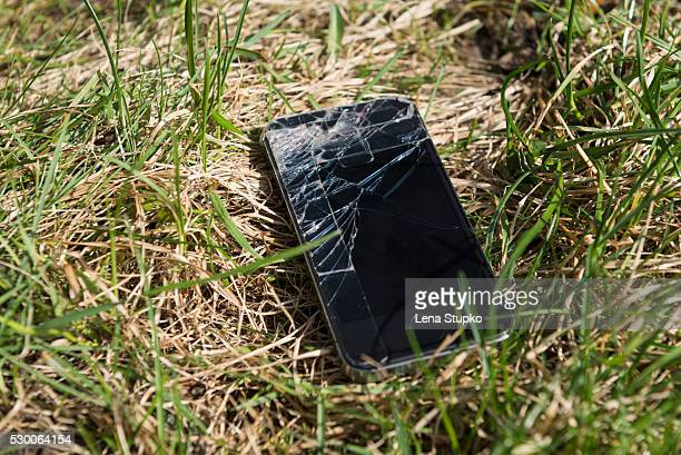 Close-up of smartphone with cracked screen lost in grassy field, Bavaria, Germany