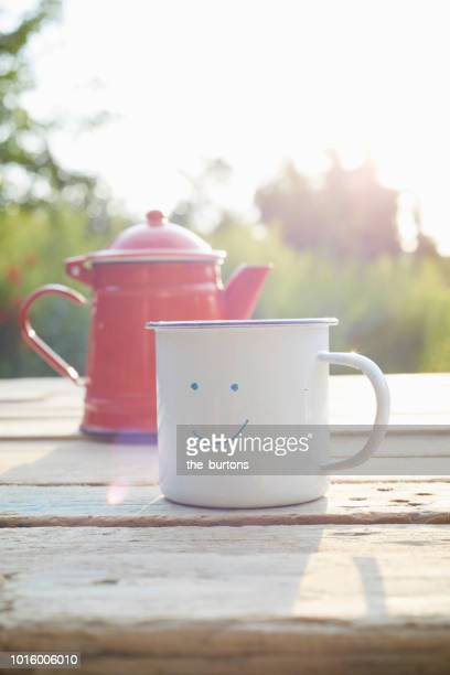 close-up of smiley face drawn on enamel mug and coffee pot on wooden table in garden - enamel stock pictures, royalty-free photos & images