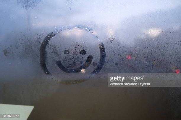 Close-Up Of Smiley Face Drawn On Wet Window
