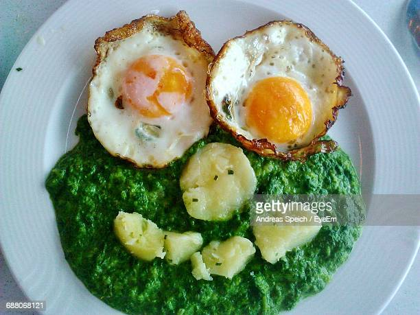 Close-Up Of Smiley Face Made From Fried Eggs And Spinach