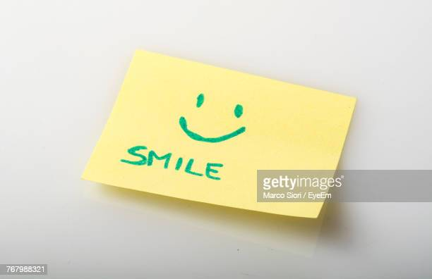 Close-Up Of Smiley Face On Adhesive Note Against White Background