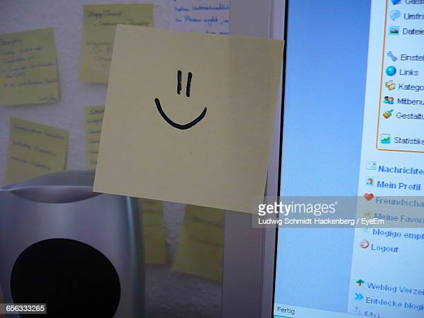 Close-Up Of Smiley Face On Adhesive Note Stuck To Monitor