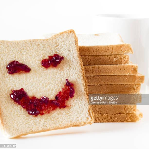 Close-Up Of Smiley Made With Preserves On Bread Against White Background