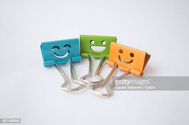 Close-Up Of Smiley Paper Clips Against White Background