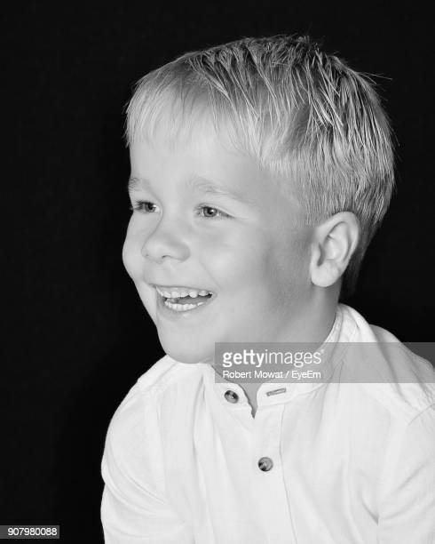 close-up of smiling boy against black background - mowat stock pictures, royalty-free photos & images