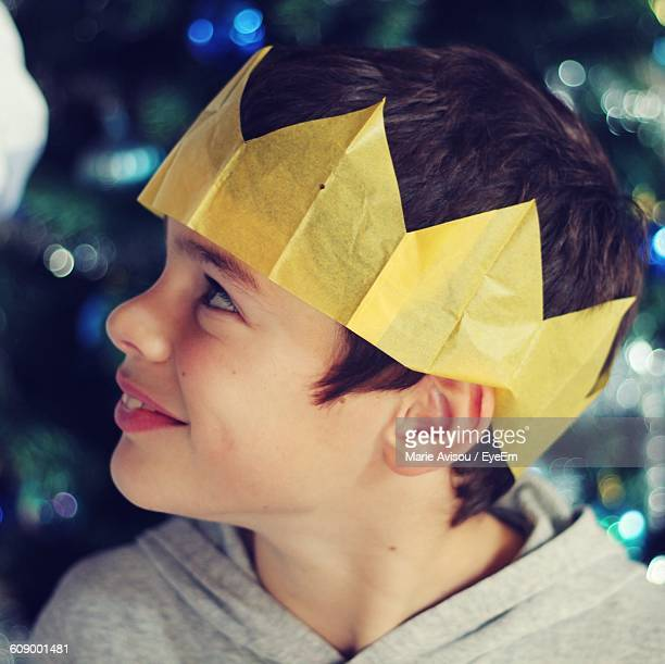 close-up of smiling boy wearing paper crown at night during christmas - crown close up stock pictures, royalty-free photos & images