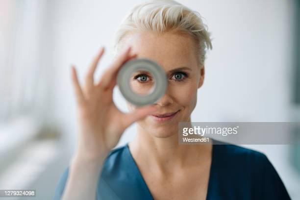 close-up of smiling businesswoman looking through object in office - scherpte stockfoto's en -beelden