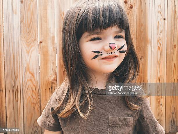 Close-Up Of Smiling Cute Girl With Painting On Face Standing Outdoors