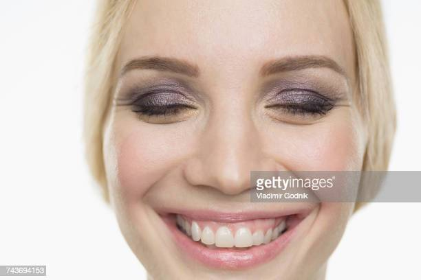 close-up of smiling fashion model with closed eyes against white background - purple eyeshadow stock photos and pictures