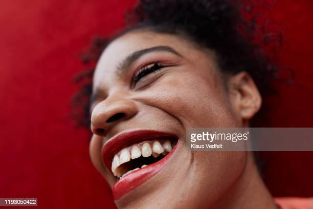 close-up of smiling female against red wall - extreme close up stock pictures, royalty-free photos & images