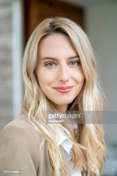 close-up of smiling female entrepreneur with blond hair in office - gray eyes stock pictures, royalty-free photos & images