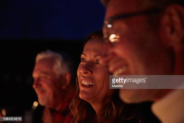 close-up of smiling friends talking during dinner party at night - candle light stock pictures, royalty-free photos & images