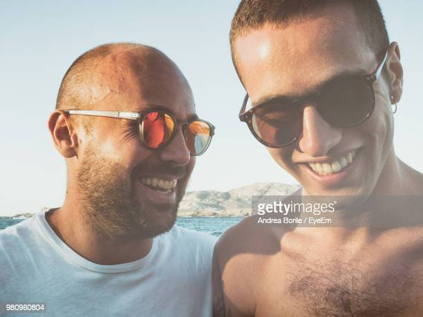 Close-Up Of Smiling Friends Wearing Sunglasses At Beach
