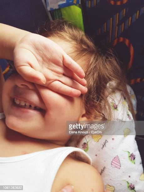 close-up of smiling girl covering eyes with hand at home - elena knouzi stock pictures, royalty-free photos & images