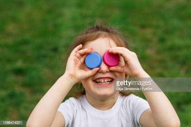 close-up of smiling girl holding bottle caps on eyes - 蓋 ストックフォトと画像