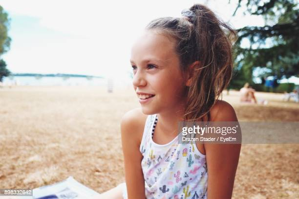 close-up of smiling girl sitting at beach against sky - drazen stock pictures, royalty-free photos & images
