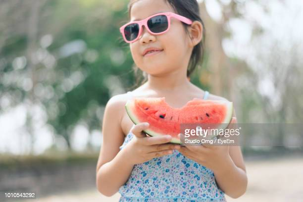 Close-Up Of Smiling Girl Wearing Sunglasses Holding Watermelon Slice