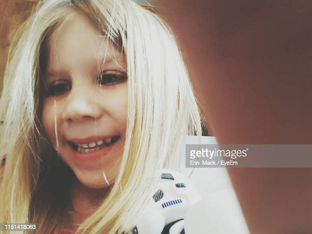 close-up of smiling girl with blond hair against wall - mack stock pictures, royalty-free photos & images