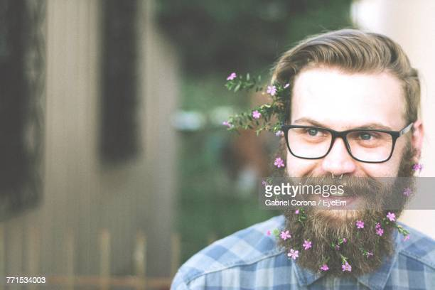 close-up of smiling hipster wearing flowers - barba peluria del viso foto e immagini stock