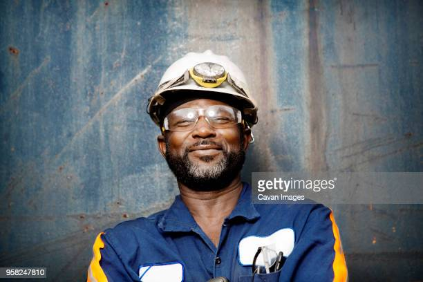 close-up of smiling male worker standing against metal wall - waste management stock pictures, royalty-free photos & images