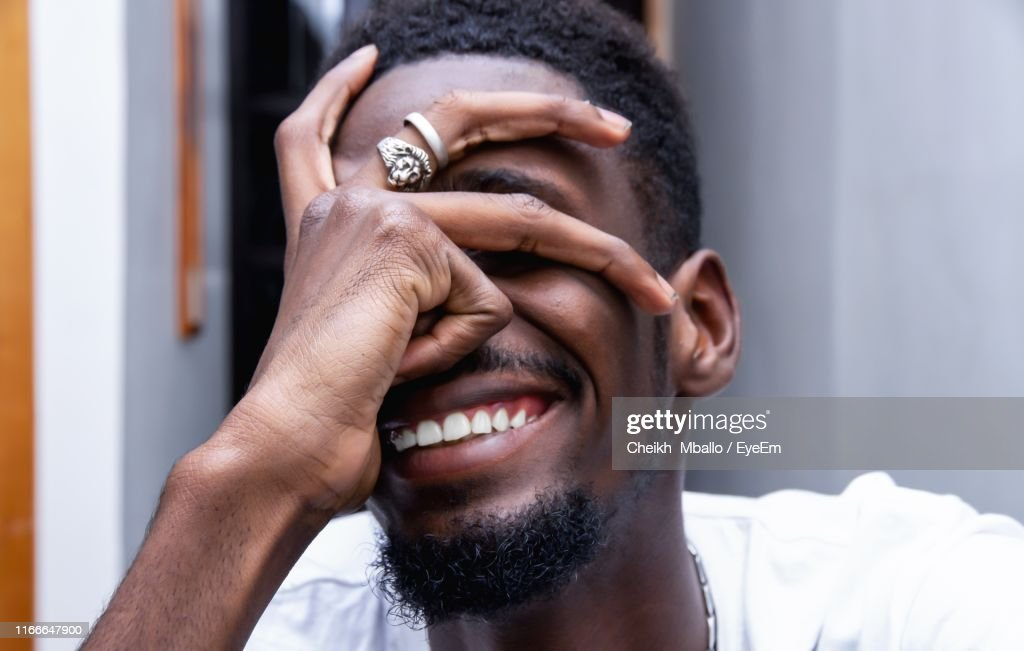 Close-Up Of Smiling Man Covering Face With Hand At Home : Stock Photo