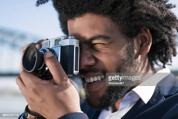 close-up of smiling man taking a picture with a vintage camera - temas fotográficos - fotografias e filmes do acervo