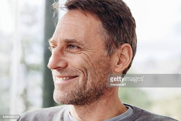 close-up of smiling mature man looking away - van de zijkant stockfoto's en -beelden