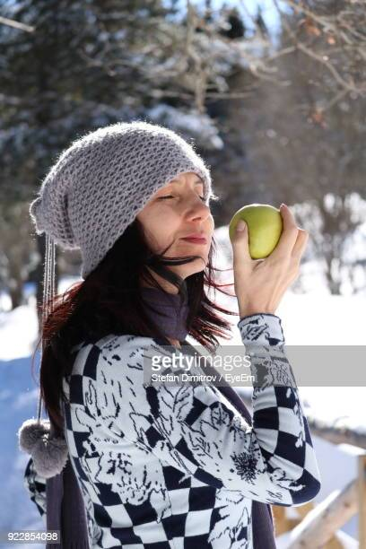 Close-Up Of Smiling Mature Woman Holding Fruit During Winter