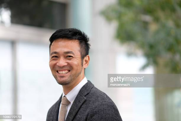 closeup of smiling mid adult businessman - east asia stock pictures, royalty-free photos & images