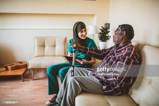 nahaufnahme des lächelnden seniors mit gehstock und freundlicher krankenschwester. freundliche betreuer im gespräch mit einem glücklichen älteren mann mit einem gehstock in einem sanatorium. eine muslimische ärztin und ihr leitender afroamerikanischer - fotostock stock-fotos und bilder