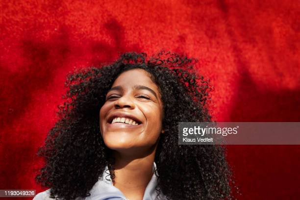 close-up of smiling woman against red wall - head back stock pictures, royalty-free photos & images