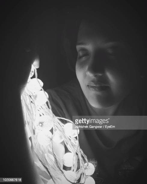 Close-Up Of Smiling Woman Holding Illuminated Light In Darkroom