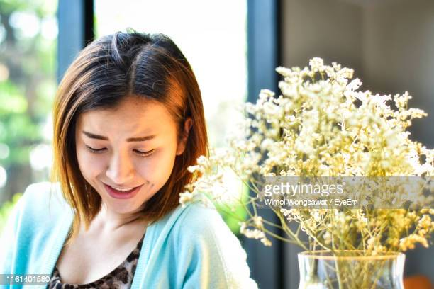 close-up of smiling woman looking down - wimol wongsawat stock photos and pictures