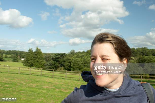 Close-Up Of Smiling Woman On Field Against Sky During Sunny Day