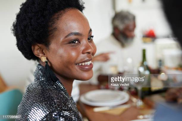 close-up of smiling woman sitting at dining table - belle femme africaine photos et images de collection