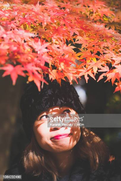 Close-Up Of Smiling Woman Standing Below Autumn Leaves
