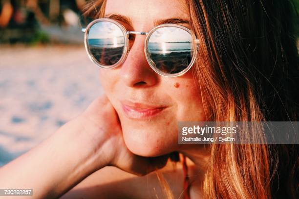 Close-Up Of Smiling Woman Wearing Sunglasses With Reflection Of Beach