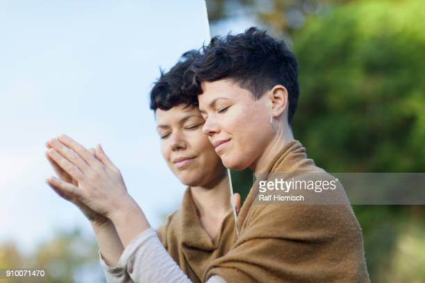 Close-up of smiling woman with closed eyes leaning on mirror at park
